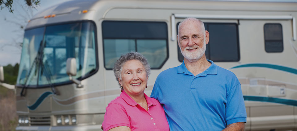 couple in front of large RV