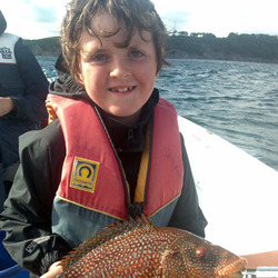 Smiling boy holding a captured wrasse fish. Photo credit @Wapster on Flickr.